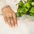 Brides hand showing off gold jewelery — Stock Photo #42497409