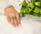 Brides hand showing off gold jewelery — Stock Photo