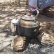 Kettle on camp fire in desert — Stock Photo