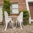 Garden chairs and table on a patio — Stock Photo #47080017