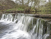 Water flowing over a small waterfall — Stock Photo