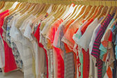 Womens summer clothes hanging on rail — ストック写真