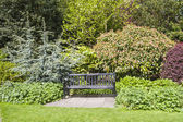 Park bench set in beautiful gardens — Stock Photo