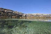 Stony seawall in tropical lagoon — Stock Photo