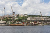 Derelict dockyard by river in city — Stock Photo