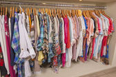 Womens clothes hanging on rail — Stock Photo
