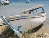 Old derelict boat abandoned on beach — Stock Photo