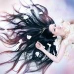 Girl lies in petals of roses — Stock Photo