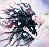 Dívka leží v okvětní plátky růží — Stock fotografie