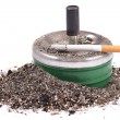 Lighted cigarette with a filter on the ashtray and ashes — Stock Photo