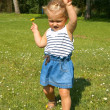 Child, a little girl having fun on the meadow, dancing with a flower in her hand — Stock Photo