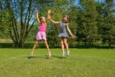 Children, girls laughing while having fun in a meadow — Stok fotoğraf