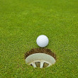 Golf, ball lying on the green next to hole — Stock Photo