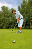 Golf, Golfer thrusting the ball into the hole — Stock Photo