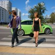 Girl and Boy, teens walking on the pedestrian crossing, behind them in the background of a passing car — Stock Photo
