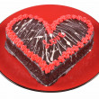 Chocolate cake in the shape of a heart with the word love on a red plate — Stock Photo #38145323