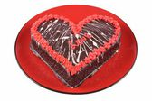 Chocolate cake in the shape of a heart with the word love on a red plate — Stock Photo