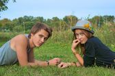 Boy and girl, teenagers lying on the grass and looking into the lens — Stock Photo