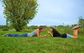 Boy and girl, teenagers lying on the grass and smiling — Stock Photo