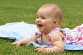 Baby, girl, seven-month-old child lying on a blue blanket — Stock Photo