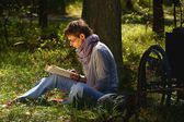 Disabled woman reading a book in the forest, wheelchair — Stock Photo