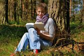 Woman reading a book in the forest — Stockfoto