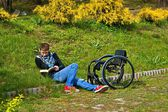 Disabled woman reading a book in the park, wheelchair — Stok fotoğraf