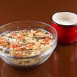 Breakfast cereals, oatmeal with candied fruits and nuts in a glass bowl and red cup milk, brown background — Stock Photo #46938855