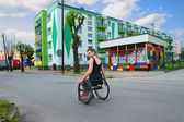 Disabled, smiling woman riding a wheelchair, down the street in the city — Stock Photo