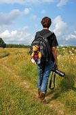 Woman photographer in the outdoors and the mascot strapped to a backpack — Foto Stock