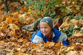 Boy, happy child playing in autumn leaves — Foto Stock