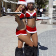 Two preety female Santa Claus offering drinks — Stock Photo #22054303