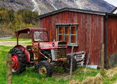 Old tractor by wooden house — Stock Photo