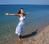 Happy young lady standing on a coastline — Stock Photo