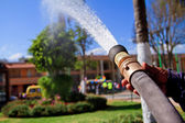 Fireman using water hose to prevent fire — Photo