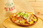 Plate of fresh nachos with a jalapeno cheese sauce — Stock Photo
