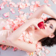 Stock Photo: Beautiful nude womwith roses eating apple