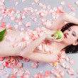 Nude woman with roses eating a green apple — Stock Photo
