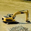 Excavator machine during earthmoving in a river, logos removed — Stock Photo