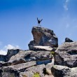Stock Photo: Young backpacker standing on top of a mountain