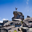 Young backpacker standing on top of a mountain - Stock Photo