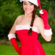 Stockfoto: Beautiful young woman in santa suit on the garden