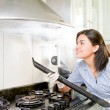 Stock Photo: Young womcleaning kitchen
