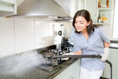 Modern kitchen - happy woman steam cleaning — Stock Photo