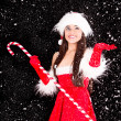 Young and sexy woman in santa costume with snow - Stock Photo
