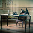 Old writing desk full of quills and typewriter — Stock Photo