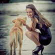 Young woman with homeless dog in the rain — Stock Photo