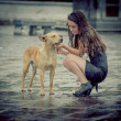 Stock Photo: Girl comforting a with dog under rain.