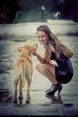 Jonge vrouw met daklozen hond in de regen — Stockfoto