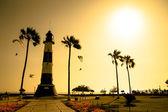 Sylwetka latarni wśród złoty zachód morze — Zdjęcie stockowe